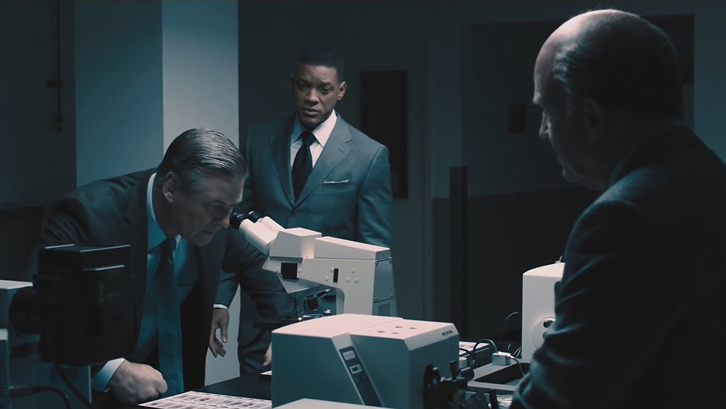 Alec Baldwin usando un microscopio, con Albert Brooks a la derecha y Will Smith de fondo