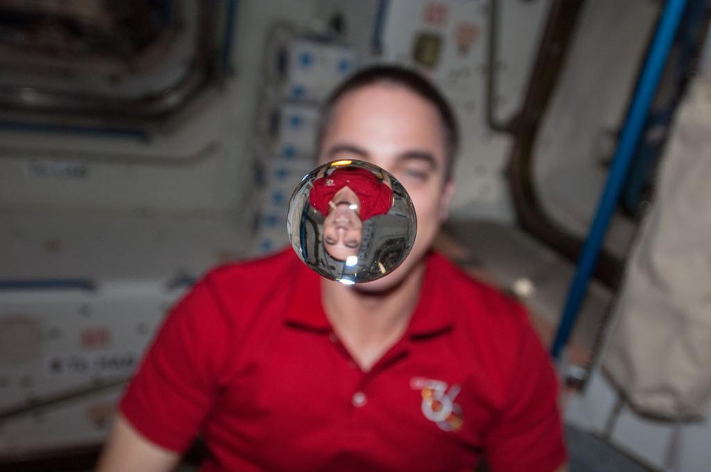 El astronauta de la NASA Chris Cassidy, ingeniero de vuelo de la expedición 36, en el nodo Unity de la Estación Espacial Internacional observa cómo una burbuja de agua flota libremente entre él y la cámara, mostrando su imagen reflejada.