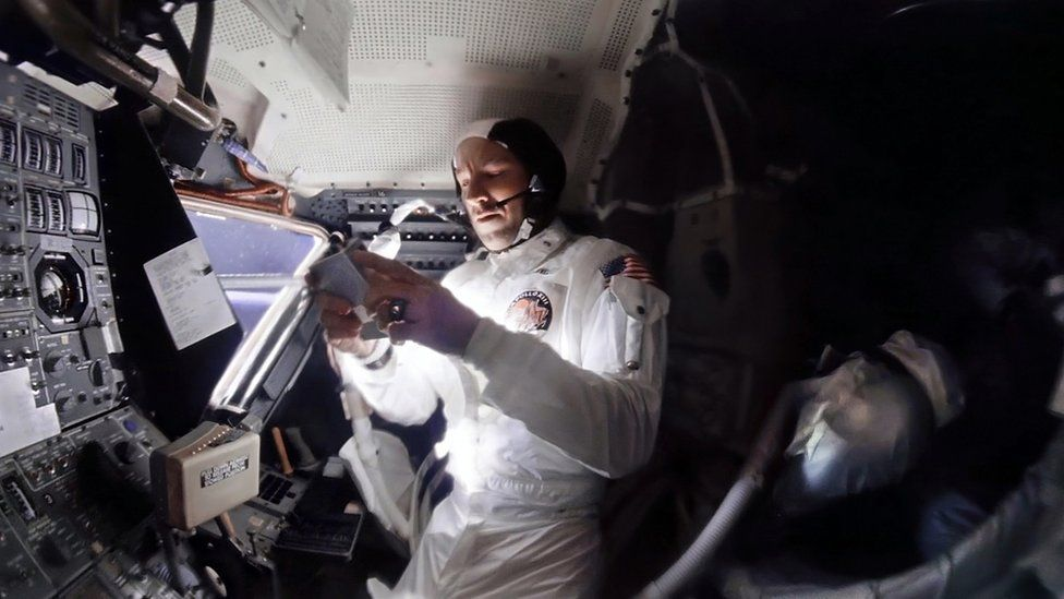 El comandante de Apollo 13, Jim Lovell, selecciona música en una grabadora portátil mientras, a la derecha, Jack Swigert toma una siesta.